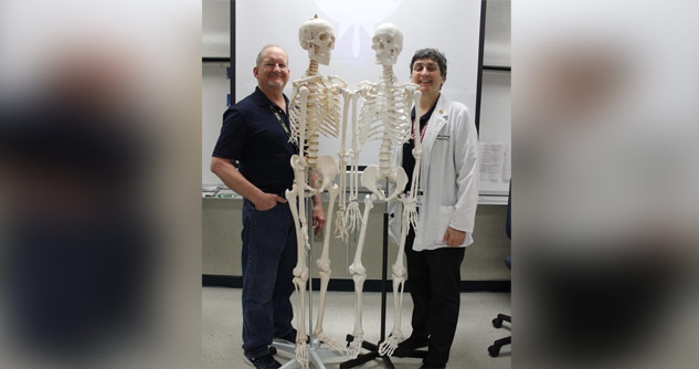 2 scientists standing next to skeletons