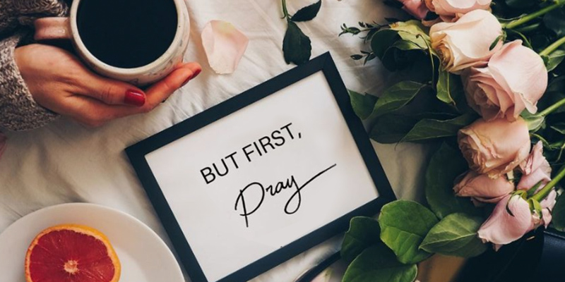 Woman holding mug, flowers, fruit and frame that says But First, Pray