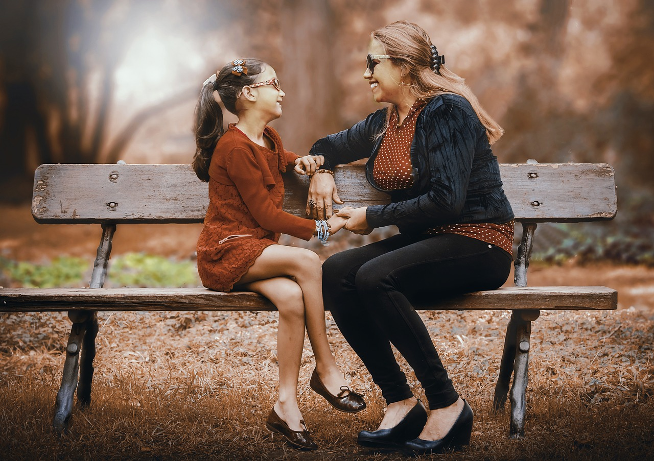 mother and daughter sitting on park bench