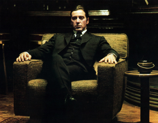 Al Pacino sitting in a large chair.