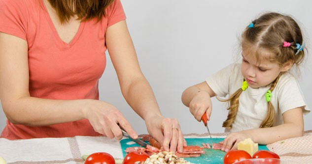 Little girl cutting chicken with mom